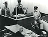 Photo Eichmann in glass booth at trial.